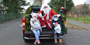 Zdjęcie przedstawia Mikołaja, który rozdaje dzieciom prezenty.