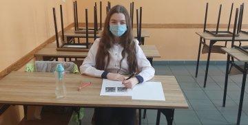 Uczennica Kamila Makarenko siedzi w ławce szkolnej i rozwiązuje zadanie konkursowe